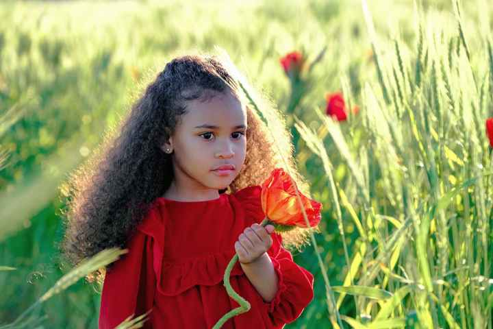 charming black girl with red flower in abundant grassland