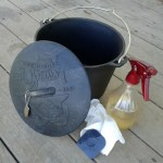 Dutch oven bean pot with a pan scraper and a bottle of apple cider vinegar and a paper towel