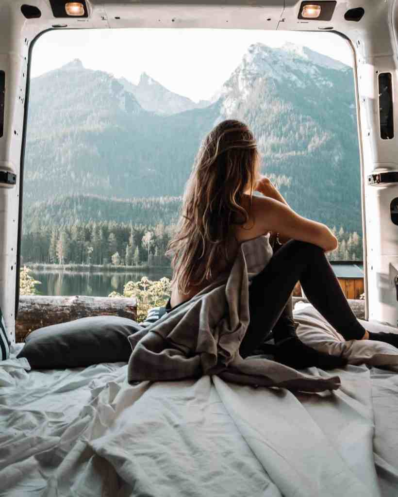 solo female traveller in the back of a van looking at the mountains
