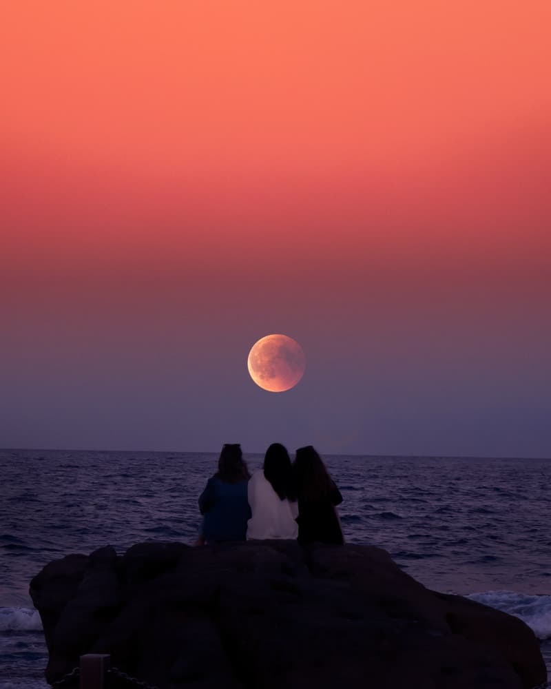 Friends watching the moon and sunset