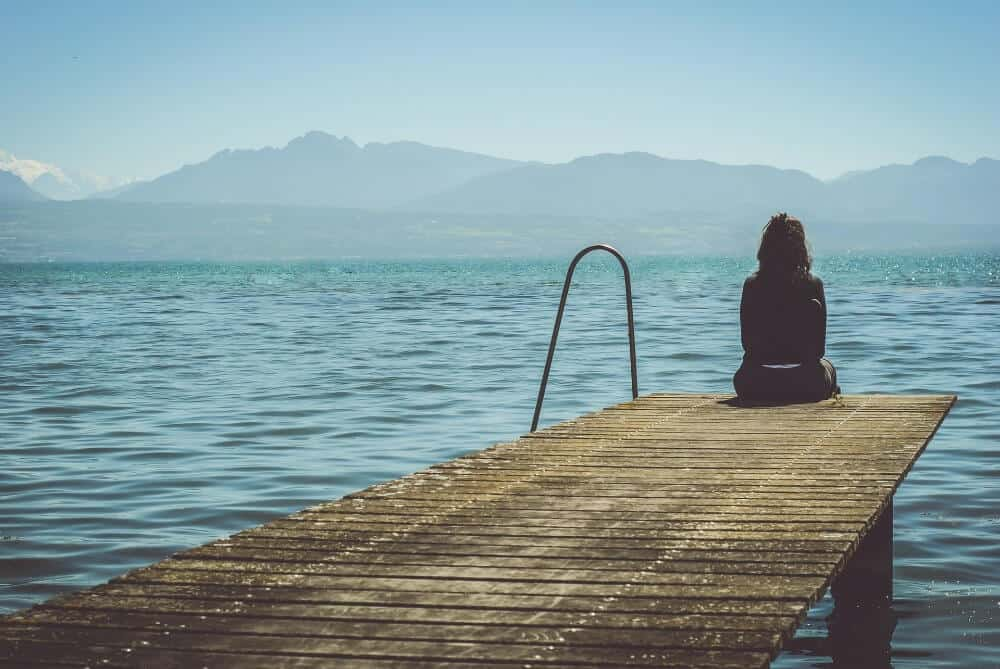 Woman sitting by a lake for post-travel depression