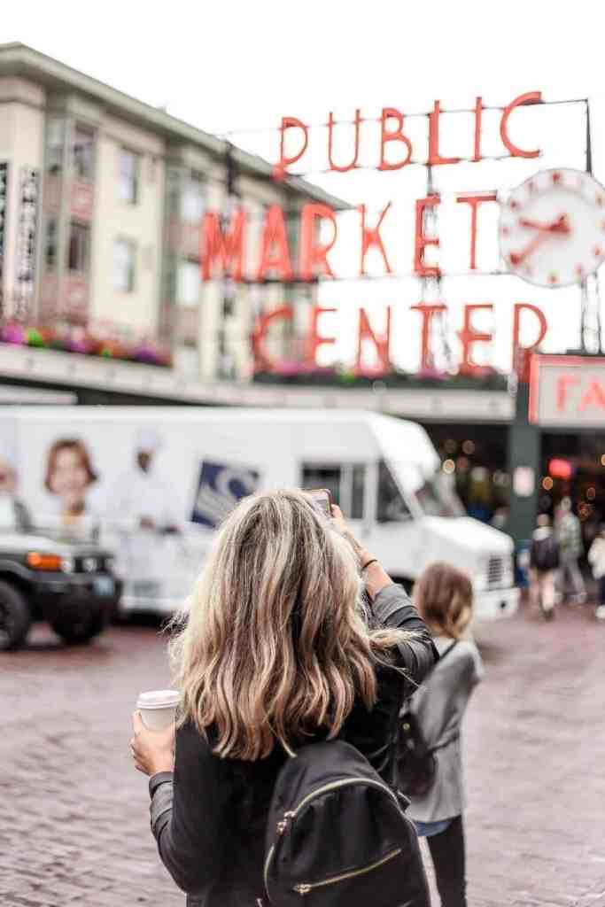 Woman taking a photo of a market sign