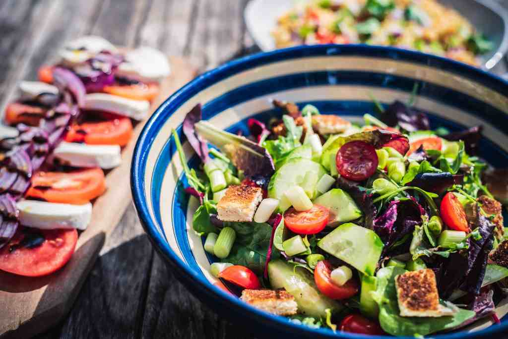 a blue and white bowl filled with salad and hallumi. A board with tomato and mozzarella next to it.