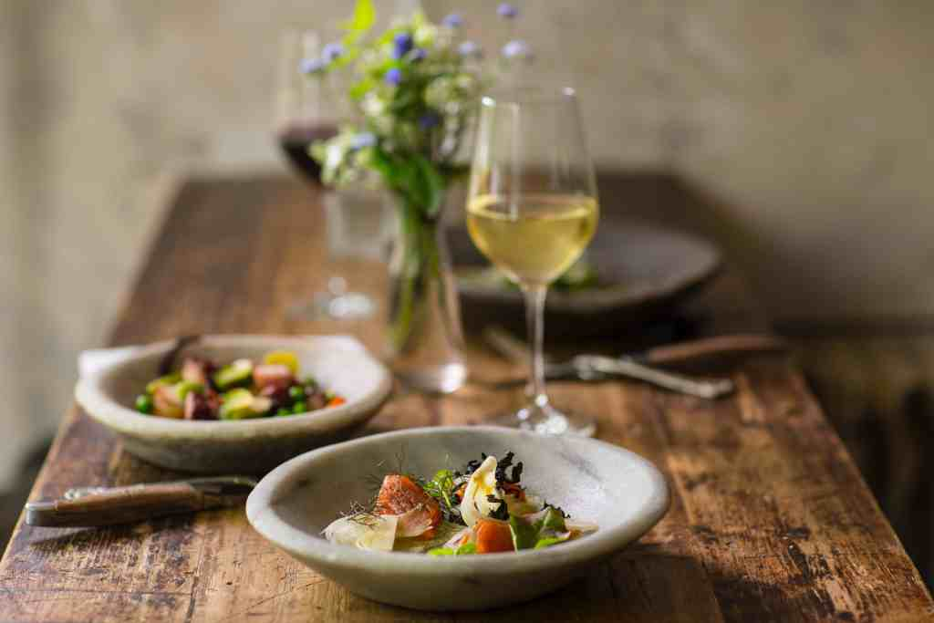Sustainable restaurants - a wooden table with a plate of food in the foreground in front of a glass of white wine. Another plate of food and flowers in the background.