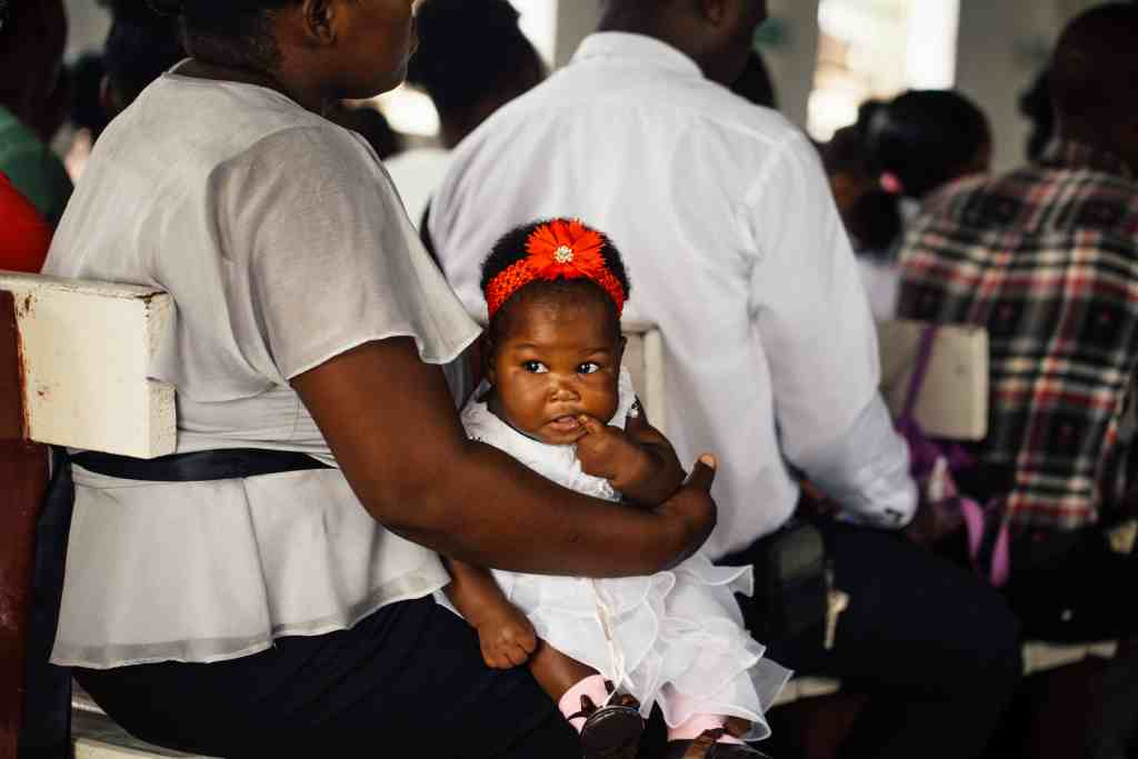 Ethical activity in the community. Baby girl sitting on mother's knee dressed in white with a red headband.