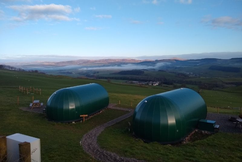 Hillhead Glamping pods with a view out towards the hills at dusk.