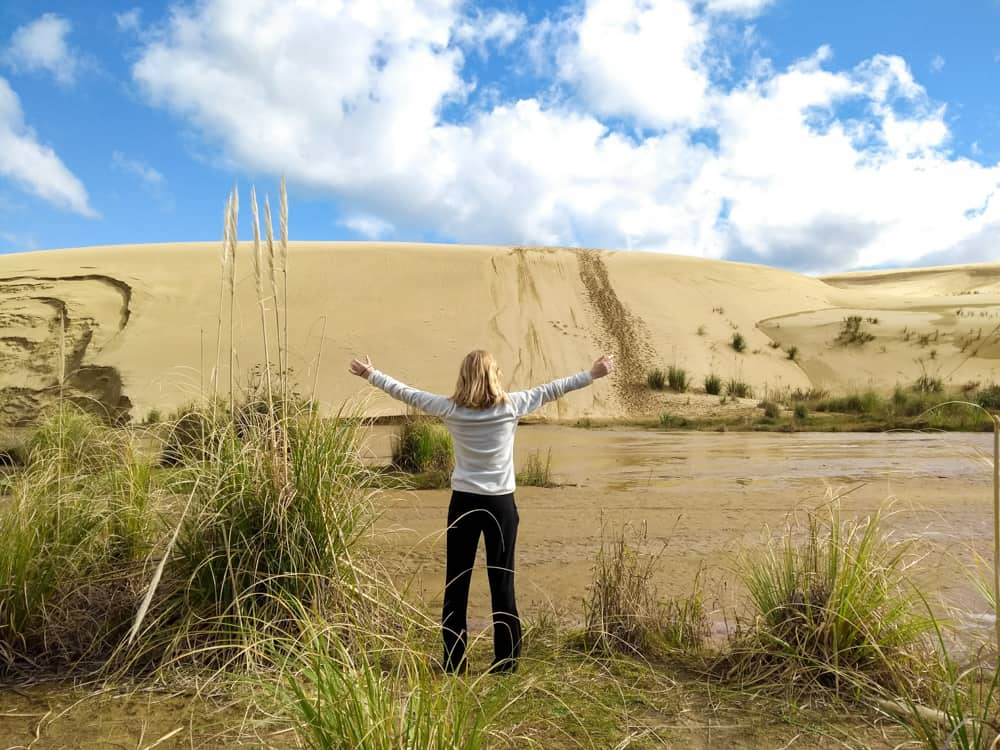 Giant Sand Dunes near Cape Reinga with a girl standing in front.