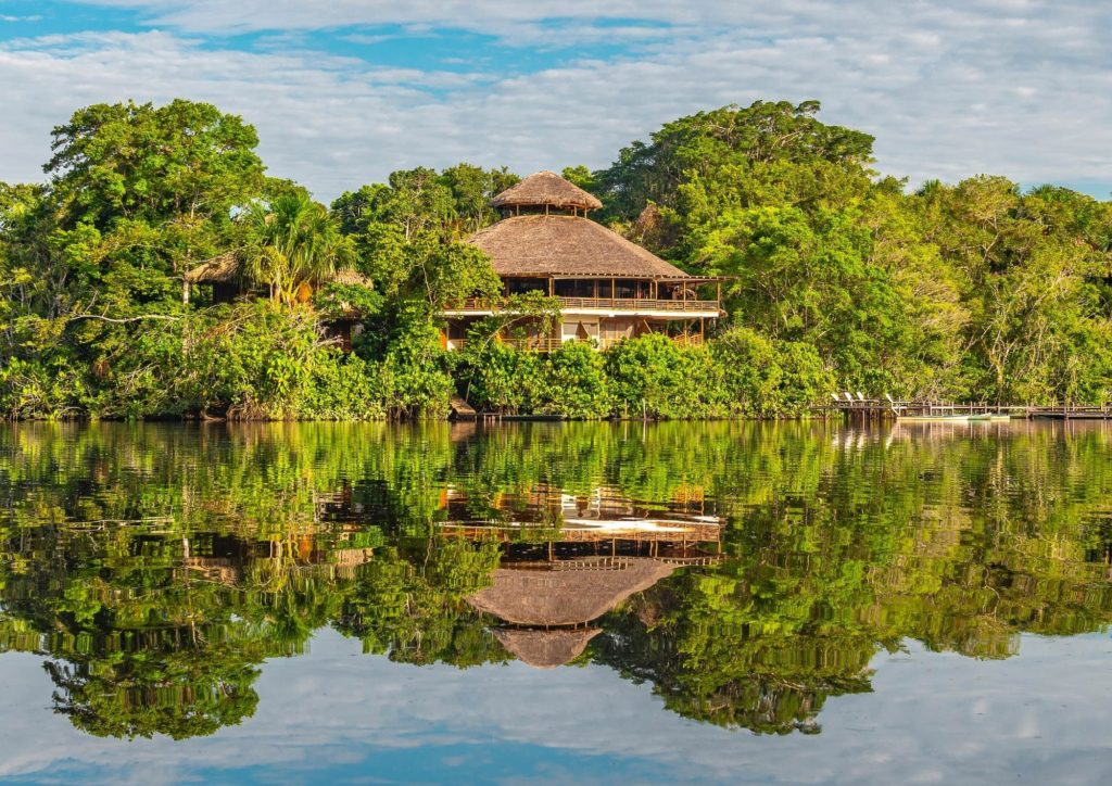 View of an ecolodge surrounded by trees across a lake