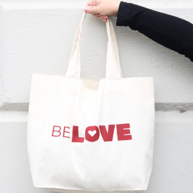 Person holding up a BeLOVE tote bag from From Belo.