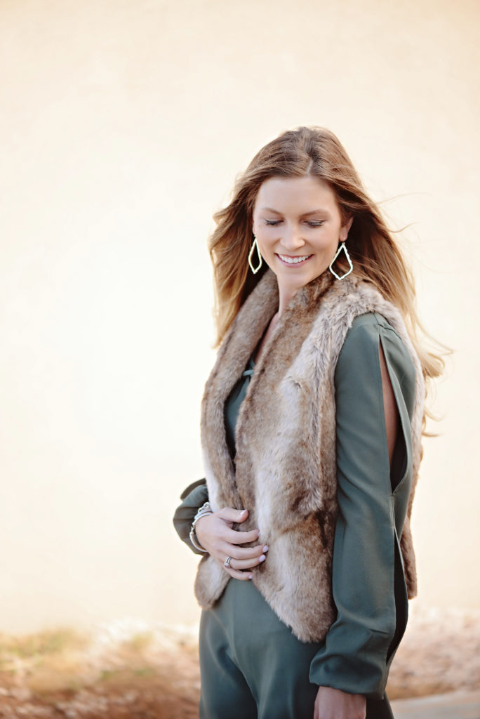 How to wear a shorts romper in the winter by layering with a faux fur vest and jacket.