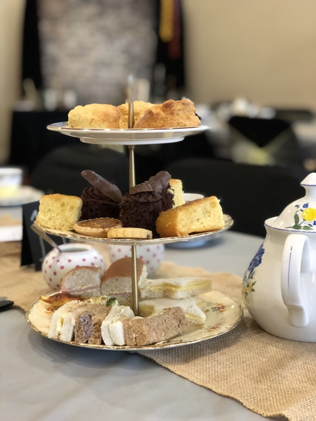 A close up of a cake stand with sandwiches and cakes at the magical themed afternoon tea