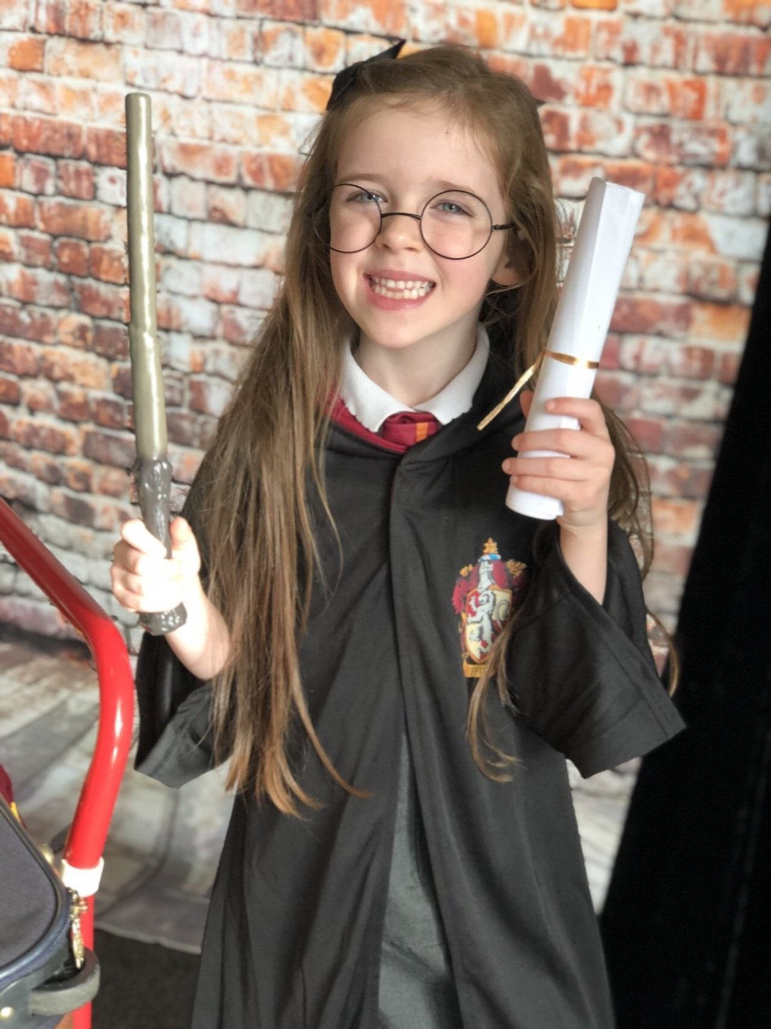 Child dressed in Harry Potter costume with wand and scroll at a magical themed afternoon tea