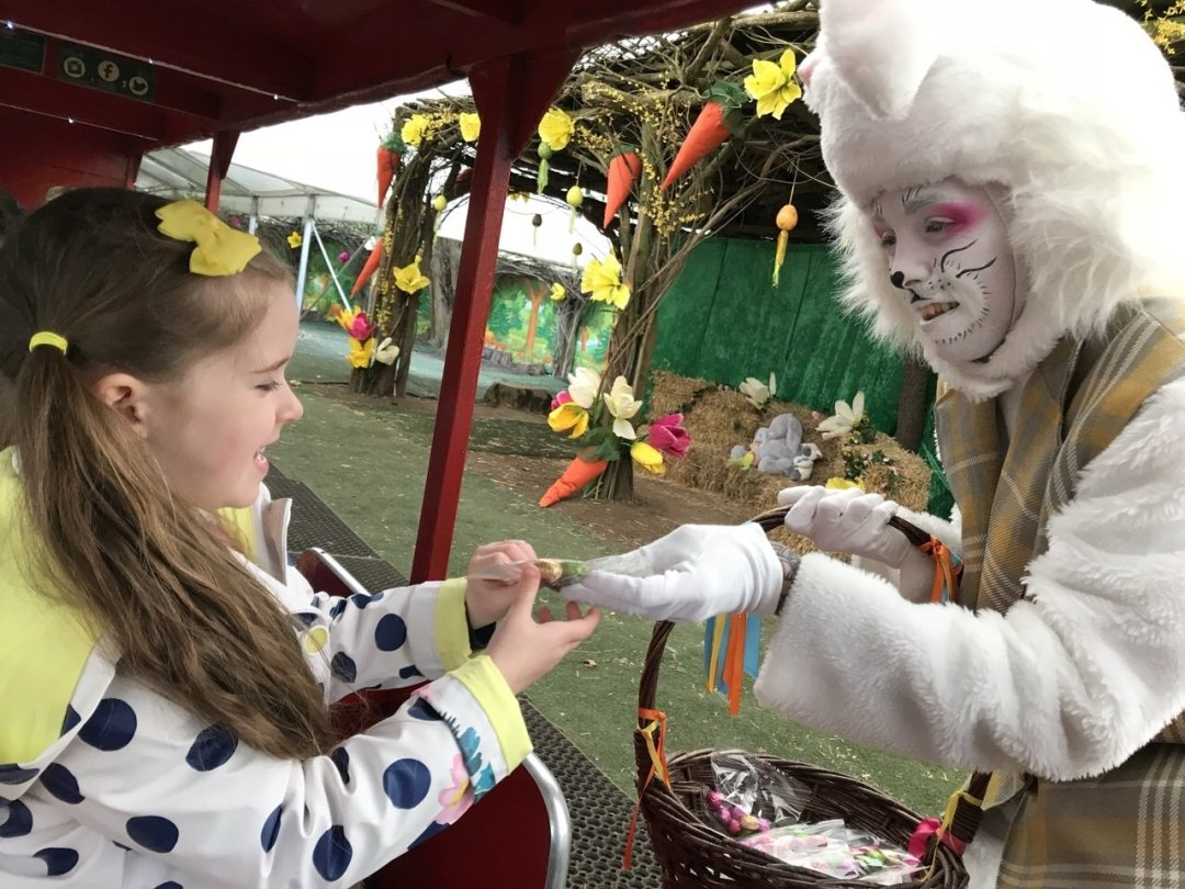 The Easter bunny handing a child an Easter treat from his basket