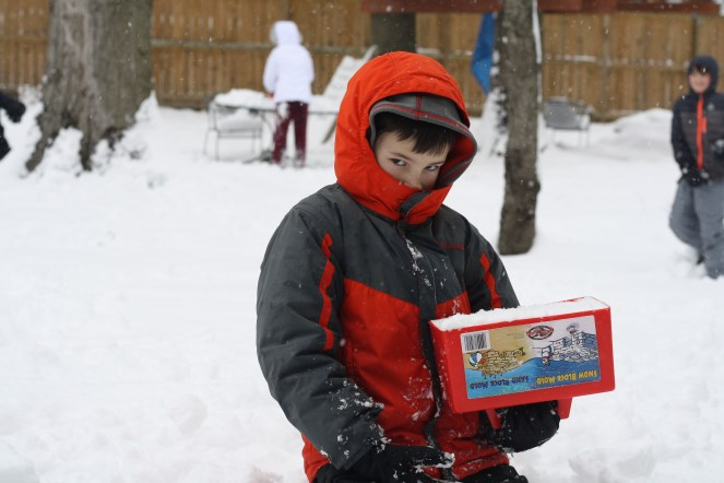 Boy playing in the snow, making snow blocks to build an igloo, with siblings throwing snowballs at him in the background