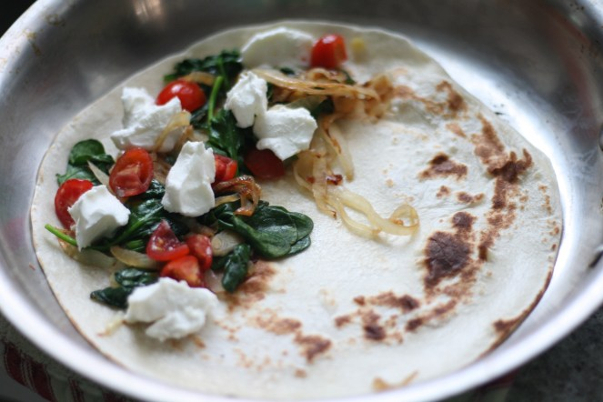 Tortilla with goat cheese crumbles, tomatoes, sautéed onions and spinach in a stainless steel pan
