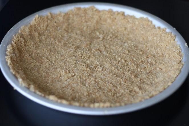 Crust in metal pie pan on a black surface