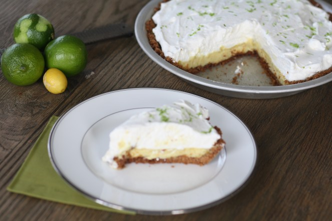 Slice of pie on a white china plate with a green napkin beneath. Limes in the corner and the remainder of the pie in the background on a wooden table.