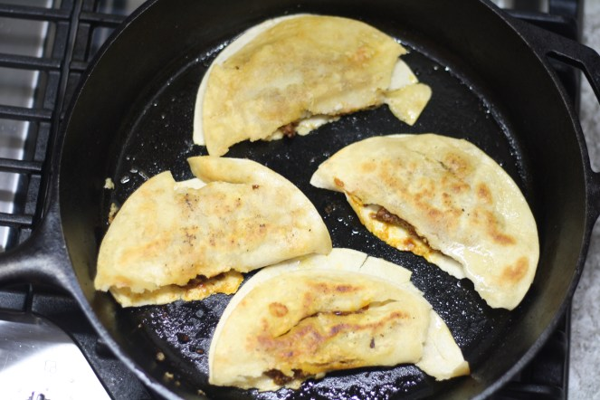 Cast iron skillet with four tacos inside, all facing upward on a stove top. The tortillas split at the fold.