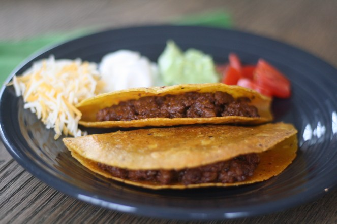 Two cooked tacos on a charcoal colored plate. On the plate above the tacos is shredded cheese, sour cream, guacamole, and diced tomatoes. The plate is on a wooden table with a green napkin underneath.