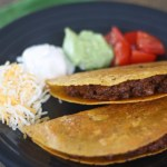 Two tacos filled with beef on a charcoal colored plate with a scoop of shredded cheese, sour cream, guacamole, and diced tomatoes on the plate behind the tacos.