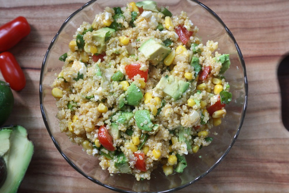 Glass bowl of quinoa salad on a wooden cutting board. To the left of the bowl is half of an avocado, face up, a lime, and two tomatoes.