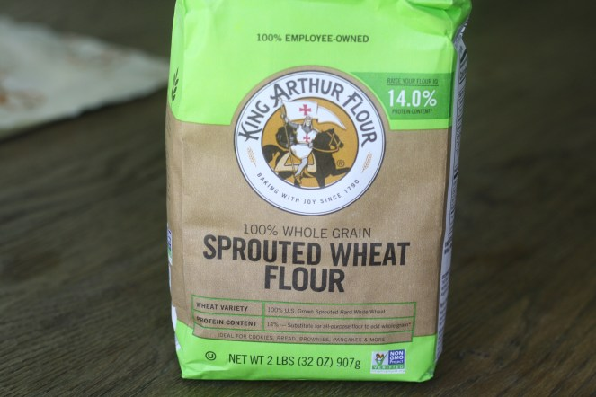 Brown and green bag of King Arthur Sprouted Wheat Flour on top of a wooden table