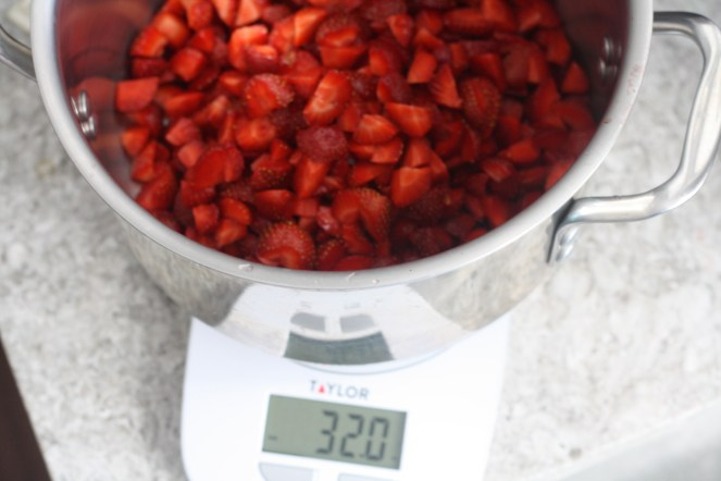 Scale showing 32 ounces of cut strawberries inside a stainless steel pot.
