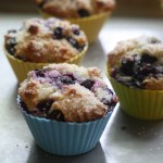 Baked blueberry muffins in silicone muffin cups on a baking sheet