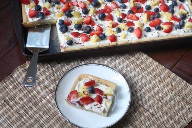 white plate with a square slice of fruit pizza. The pan of fruit pizza is in the background.