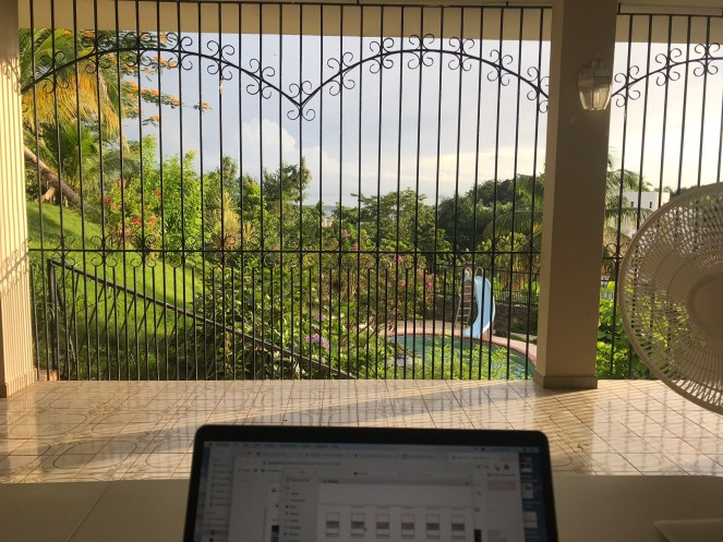 Computer on a table on an outdoor patio with pool, lush greenery and the Caribbean in the distance