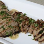 Grilled pork tenderloins sliced on white serving tray