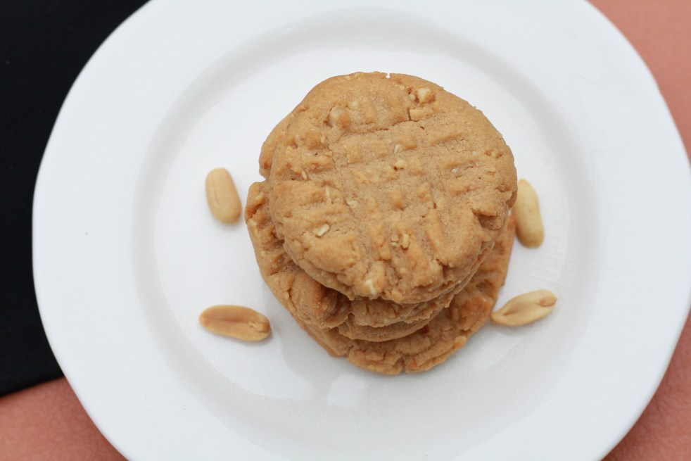 Stack of several peanut butter cookies on top of a white plate