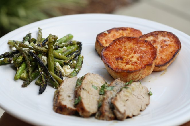 White dinner plate with pork, sweet potatoes and asparagus