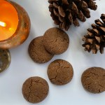 five baked molasses cookies on a white surface with pine cones and a copper candle burning in the background