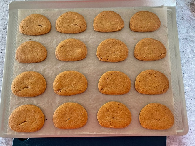 Baking sheet lined with parchment paper with 16 baked butterscotch cookies