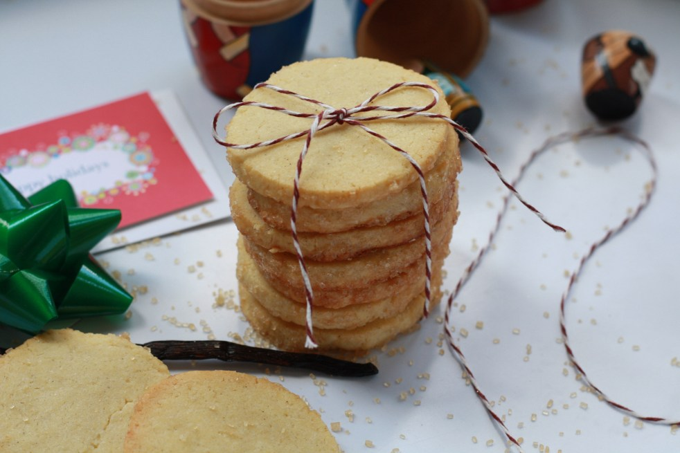 Stack of seven vanilla sable cookies tied up in red and white string. Around the cookies are various holiday wrapping items and nativity nesting dolls