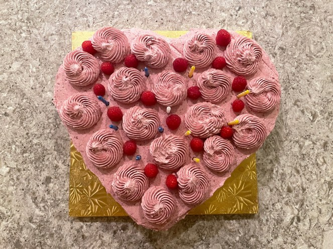 Finished chocolate-raspberry heart cake with birthday candles