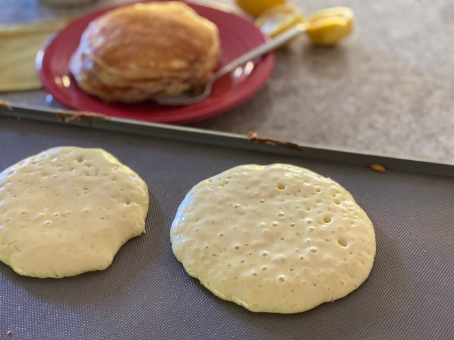Bubbles on top of pancakes cooking on electric griddle