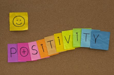 positivity concept with smiley on cork board