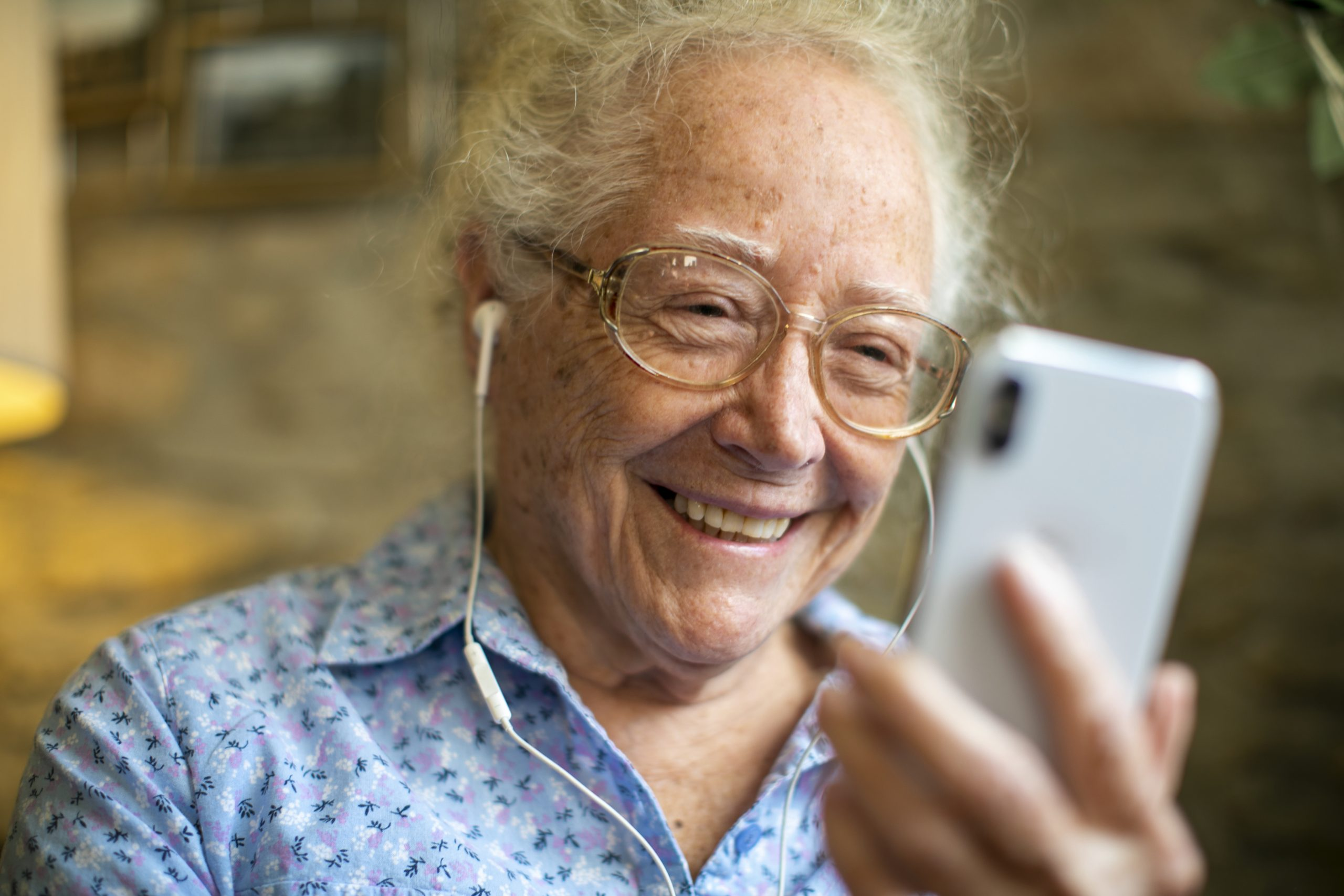 Older woman smiling and looking at smartphone