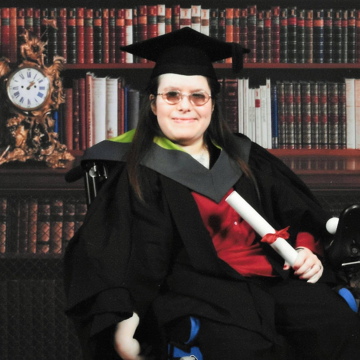 Emma's graduation photo, books behind her