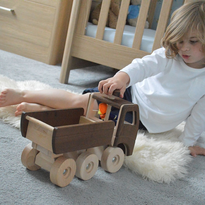 boy playing with neutral goki wooden dump truck - wooden cars