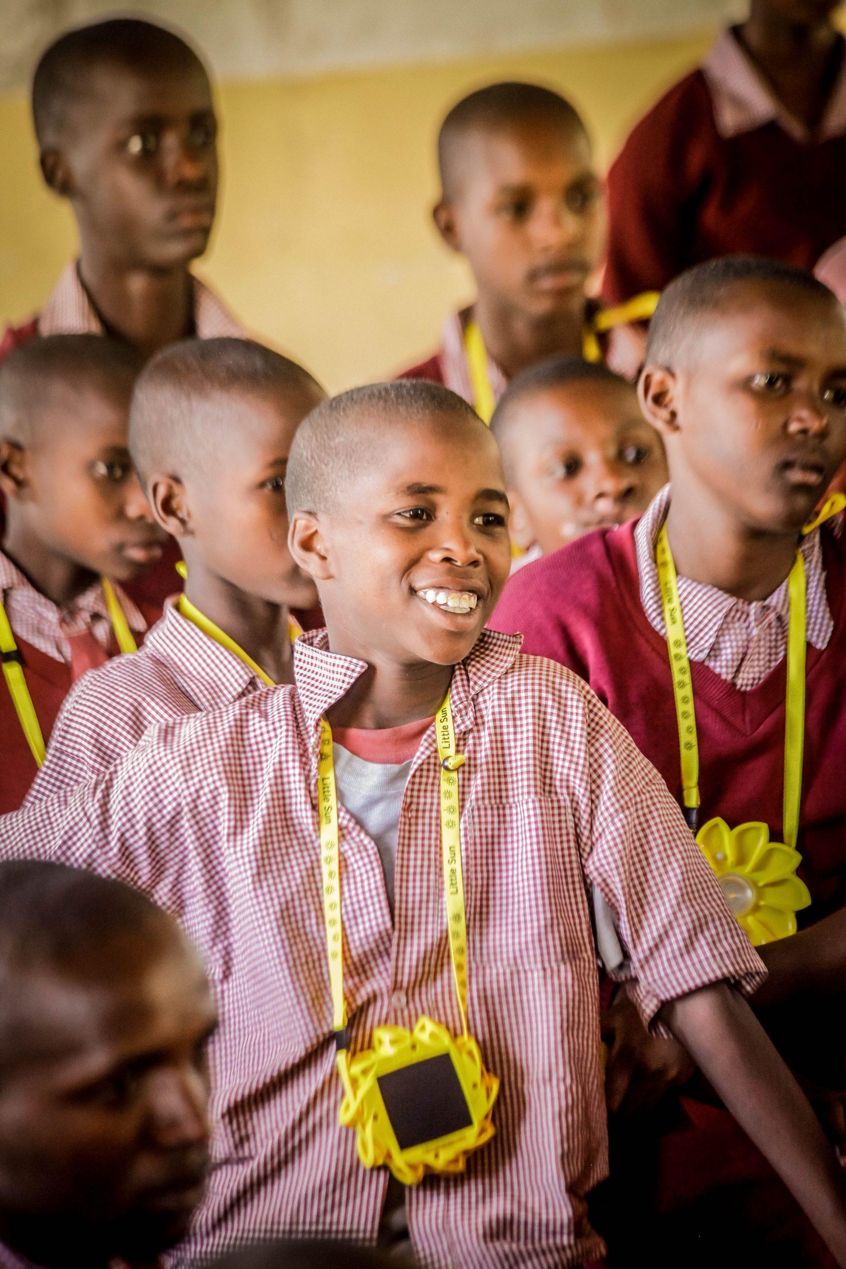 School kids wearing a Little Sun solar lamp