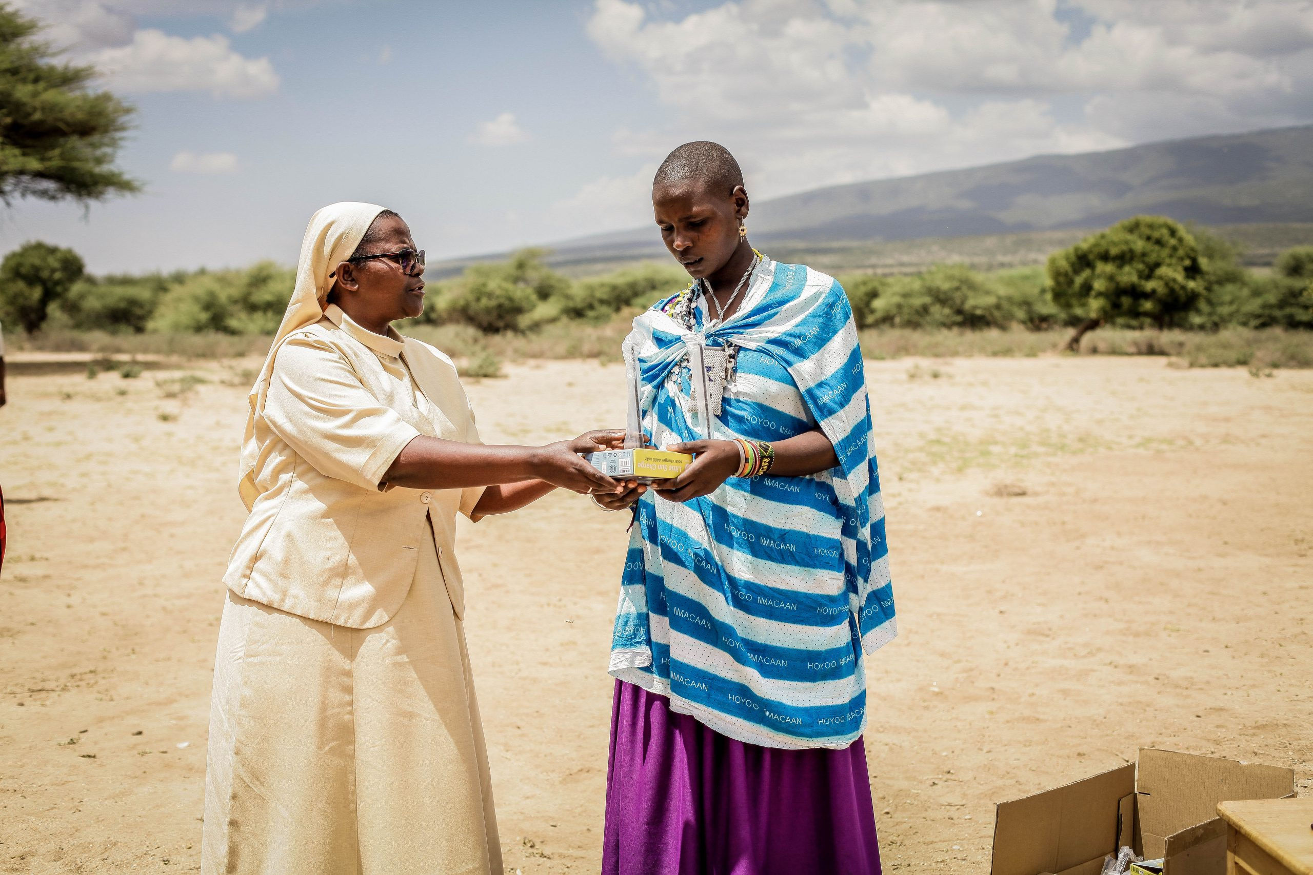 A woman distributing a Little Sun solar lamp, which is crucial for food security