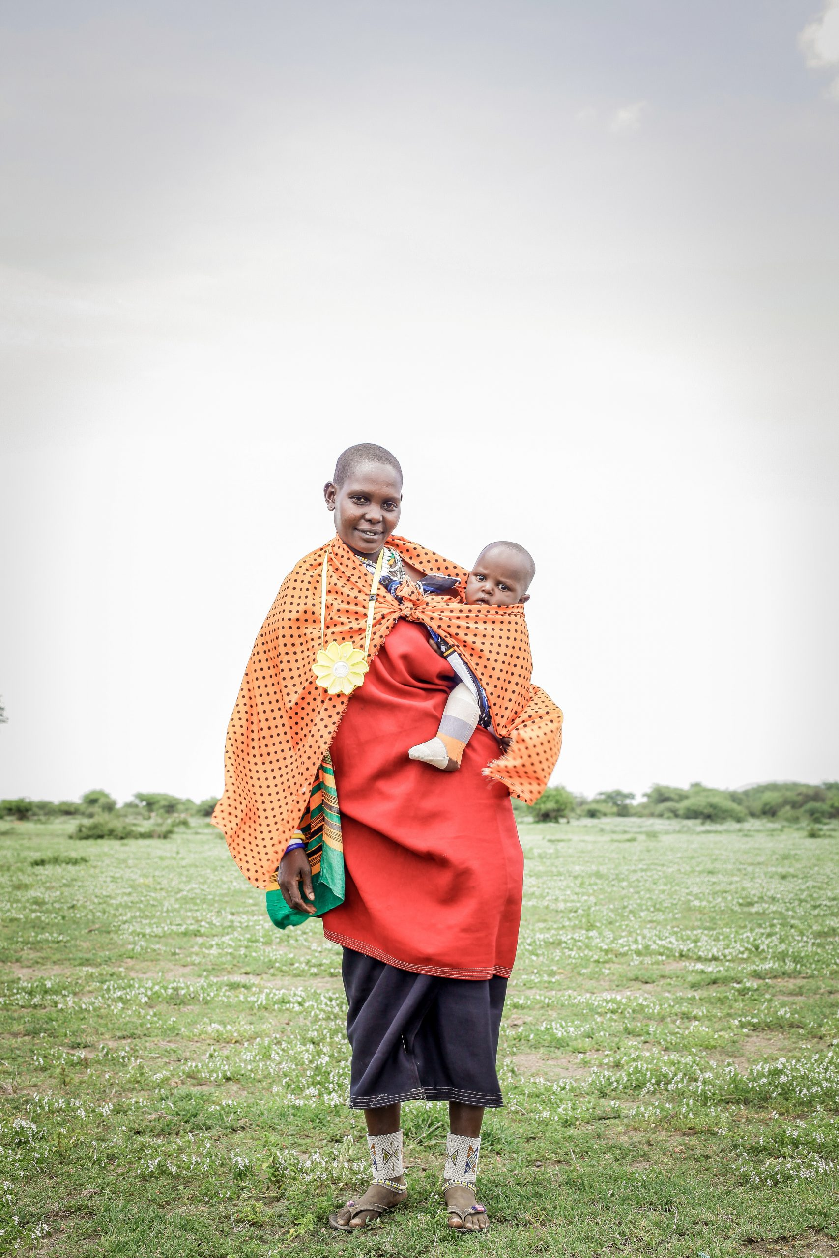 A young mother with a kid and a Little Sun solar lamp