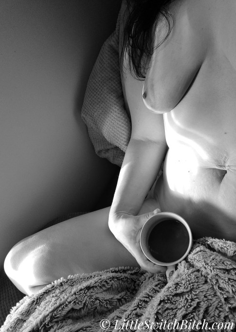 an image of a woman, in black and white, holding a cup of coffee, topless, after morning sex