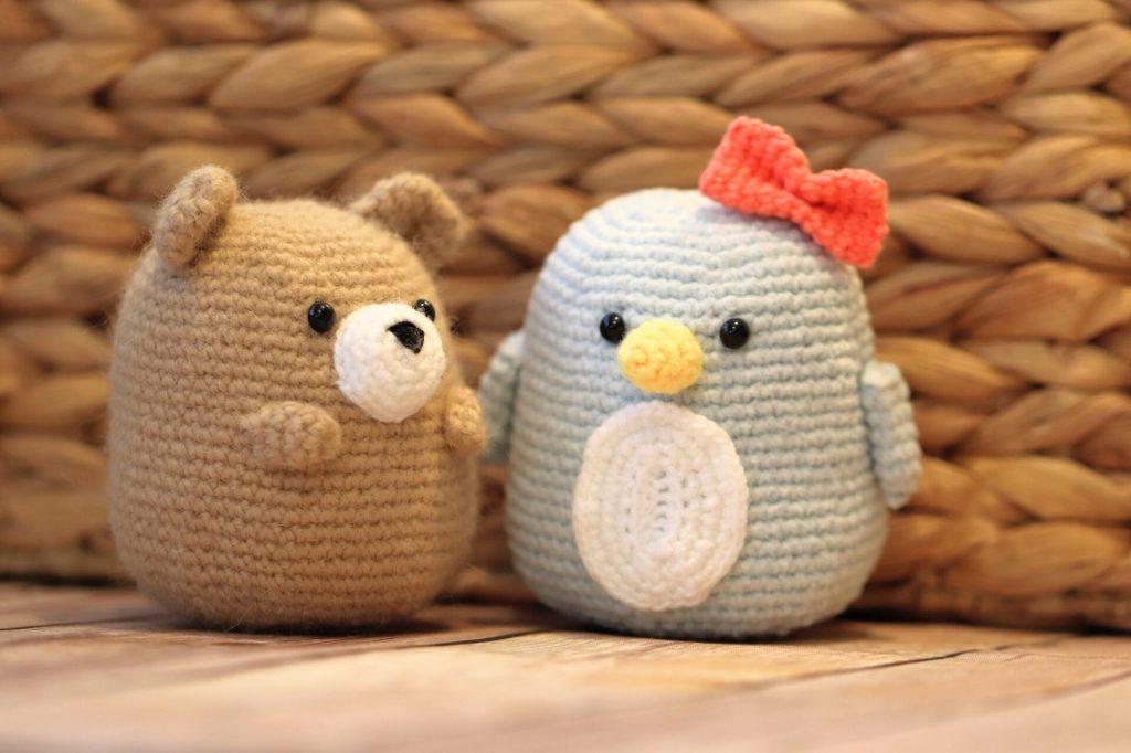 amigurumi bear and amigurumi penguin sitting next to each other