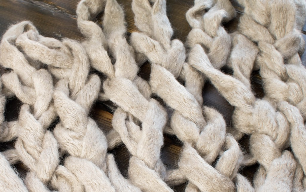 close up picture of arm knitting with large holes and gaps