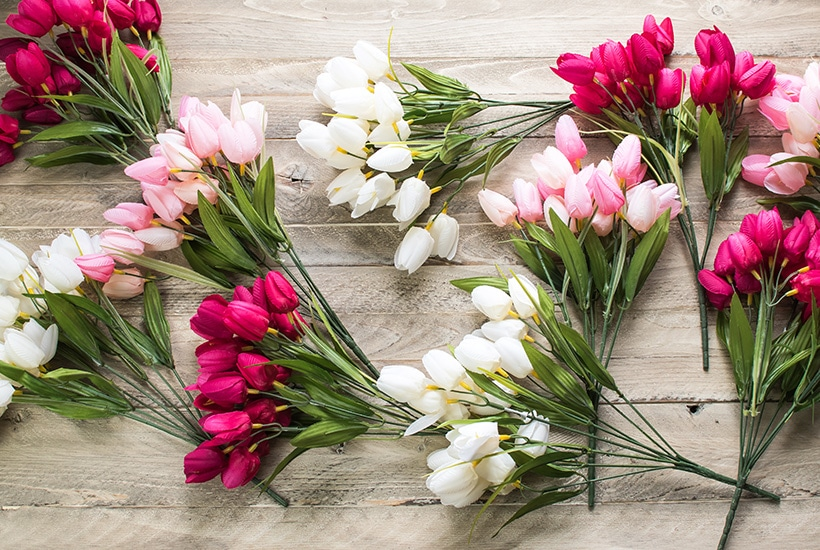 pink and white tulip sprigs spread on a wooden board