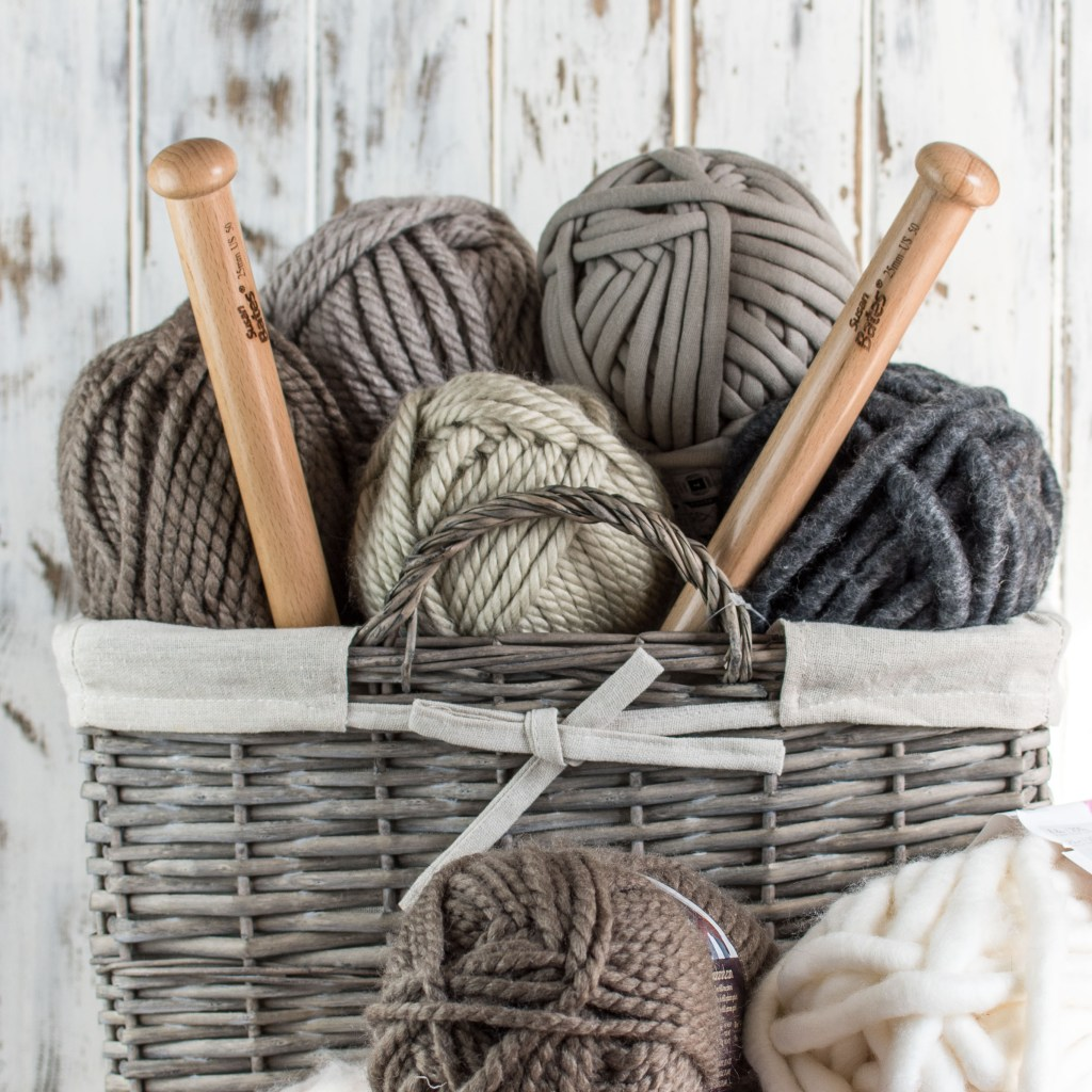 A wicker basket filled with balls of jumbo, neutral colored yarns